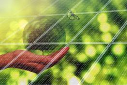 dłoń z kulą ziemską na tle panelu fotowoltaicznego